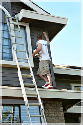 Painter working on exterior of house