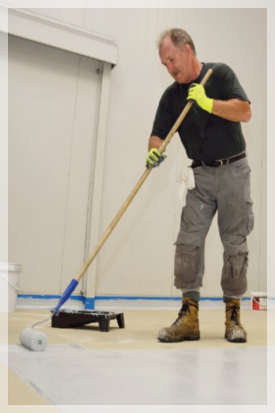 man applying an epoxy coating to a commercial floor